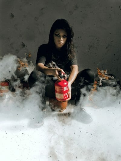 woman in black shirt holding red fireextinguisher 3645458